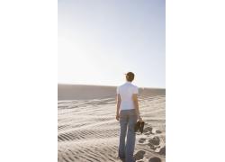 光脚走在沙漠中的女人背影
