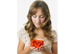 捧玫瑰花的外国卷发女人图片