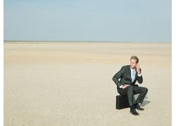 外国商业男人坐着皮箱上打手机