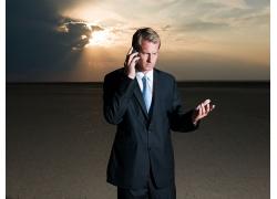 夕阳西下在打手机的外国男人