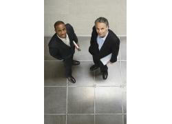 两个抱着文件的抬头看的商务男士
