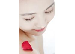 长相甜美的女孩看着肩膀上红色的玫瑰花瓣图片