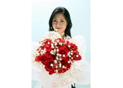 手拿玫瑰花面带微笑的漂亮女孩图片