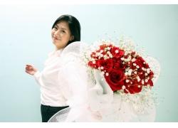 手拿玫瑰花开心微笑的美女图片