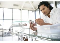 办公室里拿着手机发短信的国外男人图片