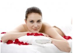 床上的SPA女人和玫瑰花瓣