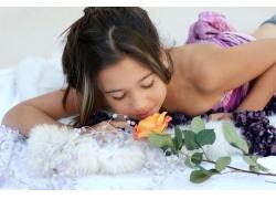 床上闻玫瑰花香的女孩