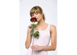 拿着一支玫瑰花的女人
